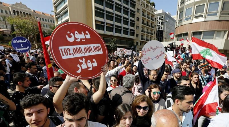 Activists carry placards reading 'No for more taxes,' during a protest in Beirut. (NABIL MOUNZER / EPA)  via pow.photos