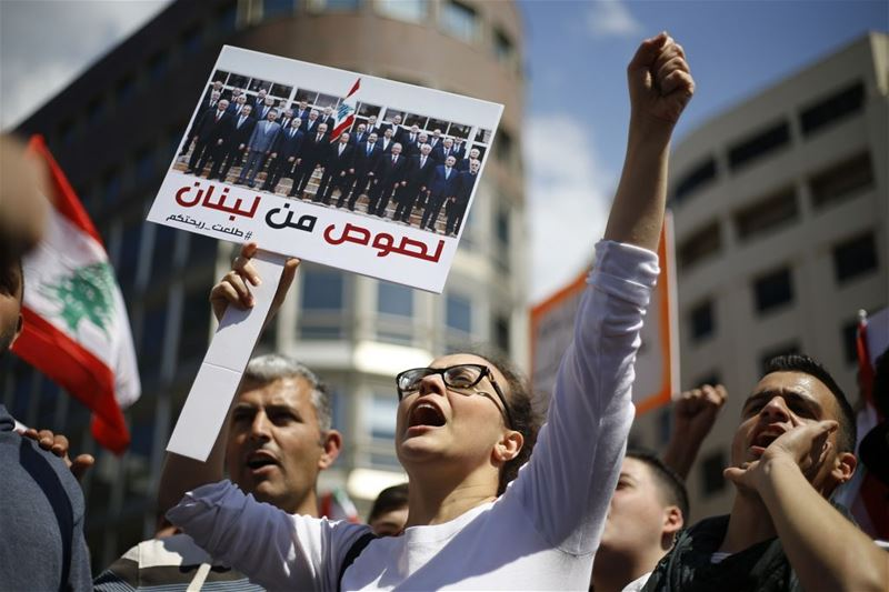 "A demonstrator with a photo of the government written on it ""Thieves of Lebanon"", in Beirut. (Bilal Hussein / AP) via pow.photos"