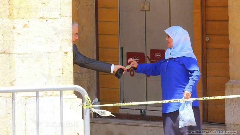 MP Ammar Houry, giving 10,000 L.L. to a woman, after a demonstration against the extension of terms for members of the parliament happened in the same area, in Beirut, Lebanon. (Hussien Baydoun / Alaraby Aljadeed)