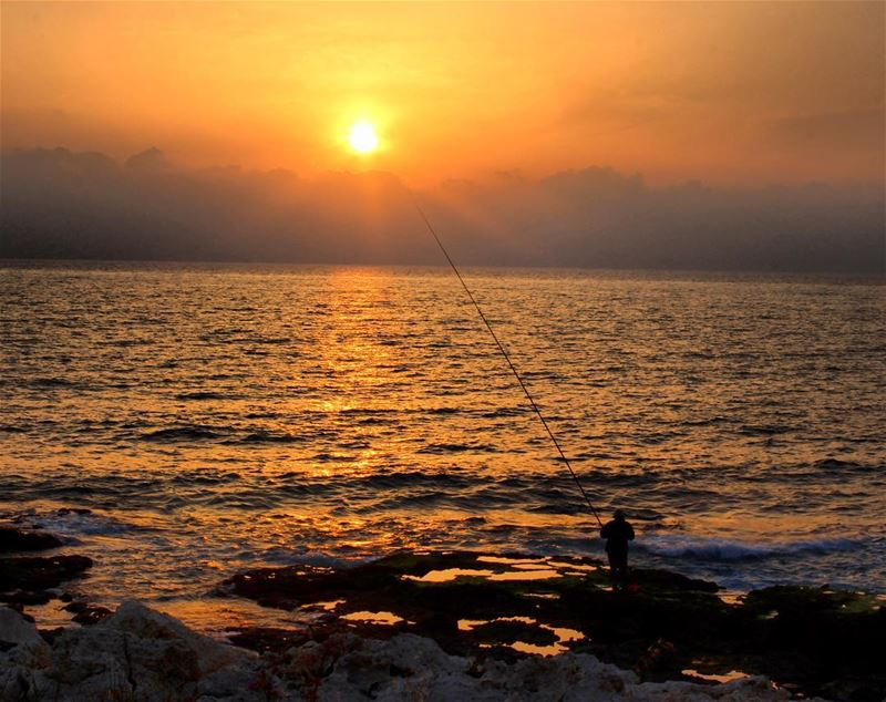 Trying to catch the sun or a fish fishermen  sunset  sky  clouds  sun ... (El Rmaileh, Mont-Liban, Lebanon)